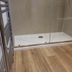 Modern shower cubicle and wooden flooring