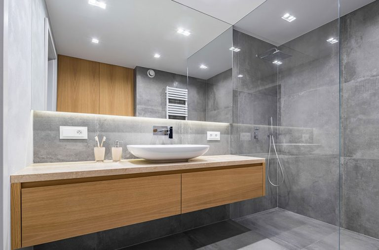 Modern bathroom with a wooden countertop, shower, basin and a big mirror