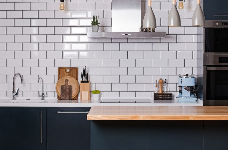 Modern kitchen with wooden worktops and white tiling